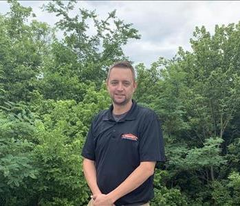 Male employee outdoors wearing black SERVPRO shirt standing in front of trees